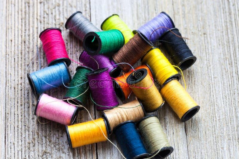 Bobinas coloridas com as linhas de costura empilhadas acima no fundo de madeira rústico fotografia de stock royalty free