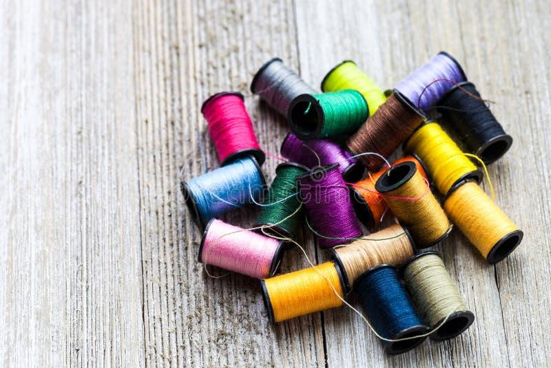 Bobinas coloridas com as linhas de costura empilhadas acima no fundo de madeira rústico com espaço da cópia fotos de stock royalty free