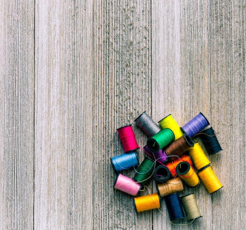 Bobinas coloridas com as linhas de costura empilhadas acima no fundo de madeira rústico com espaço da cópia fotografia de stock royalty free
