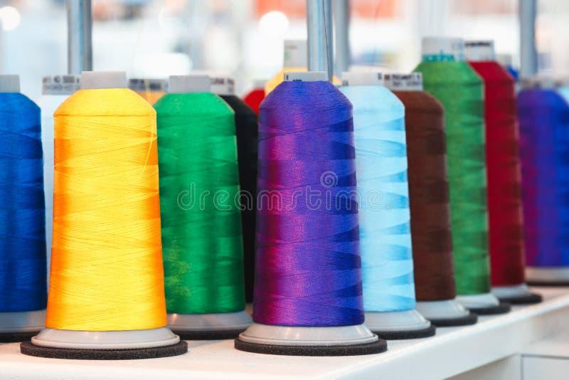 Bobinas con el hilo coloreado para las máquinas de materia textil industriales foto de archivo