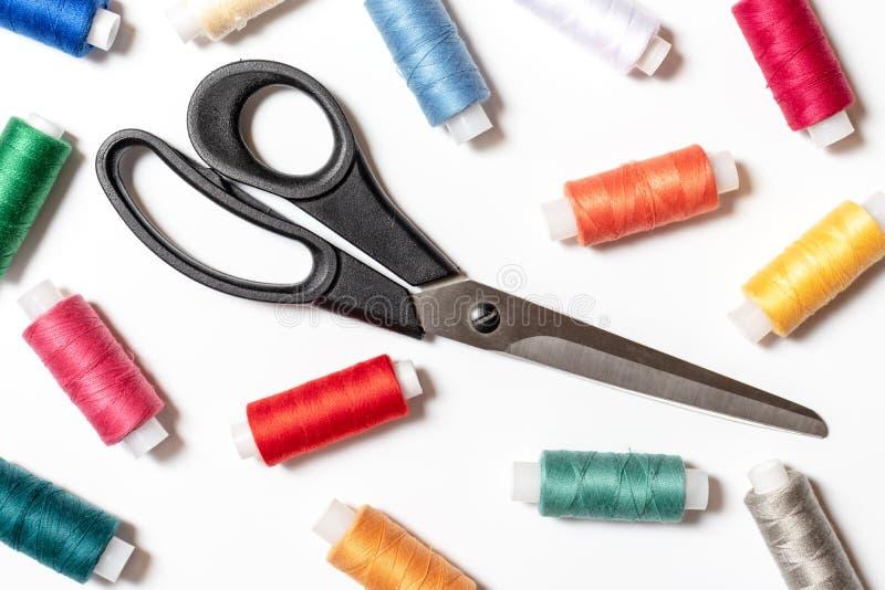 Bobinas e tesouras coloridas da linha no conceito branco do fundo, costurar, o feito a mão e do DIY - projeto para a costureira e imagens de stock royalty free