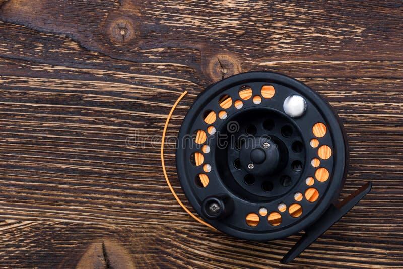 Bobine avec la ligne de pêche orange pour des mensonges de canne à pêche sur un fond en bois foncé image libre de droits