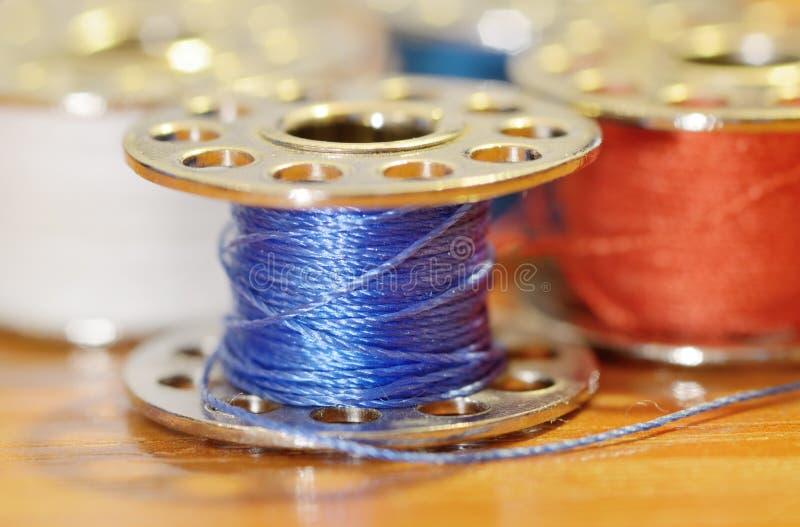 Bobine avec un fil de couture images stock