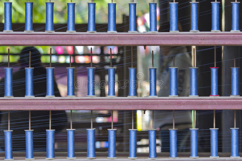 Bobine blu del filo del filato alla macchina di fabbricazione. immagine stock libera da diritti