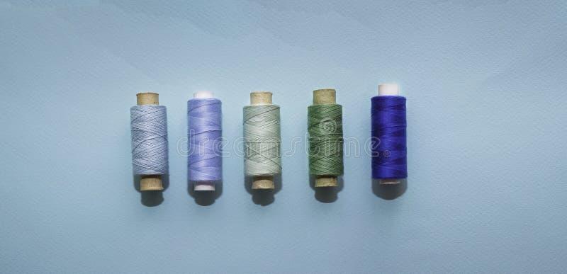 Bobine blu del filo per il cucito su un fondo blu Concetto di cucito blu e verde, cucito, fatto a mano immagini stock