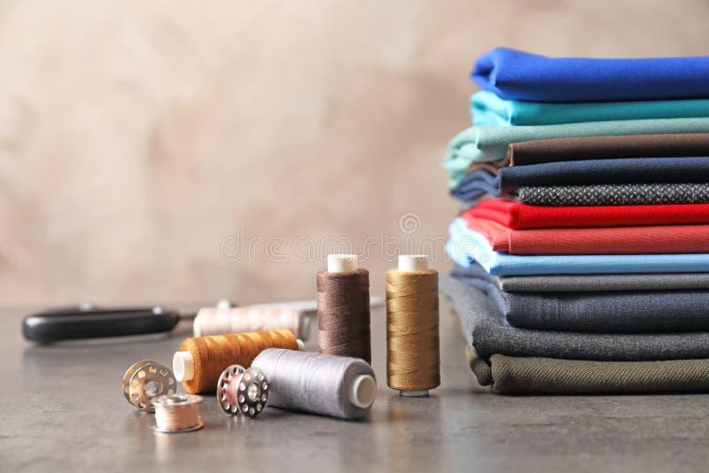 Bobine con i fili e la pila di tessuti sulla tavola Adattamento degli accessori fotografia stock