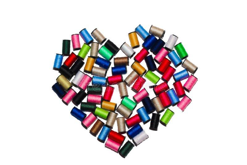 Bobine con i fili multicolori sotto forma di un cuore su un fondo bianco fotografia stock