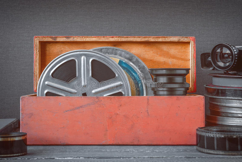 Bobine con i film in una scatola di legno, in lente ed in una vecchia cinepresa fotografie stock libere da diritti
