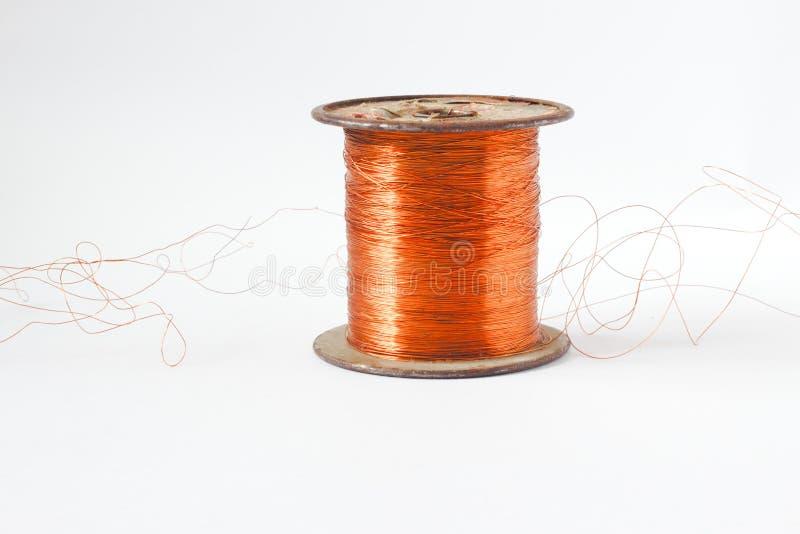 Bobine de câblage cuivre Le rouge a isolé le fil enroulé sur l'axe en plastique L'extrémité du fil est dépouillée montrant le cui image stock