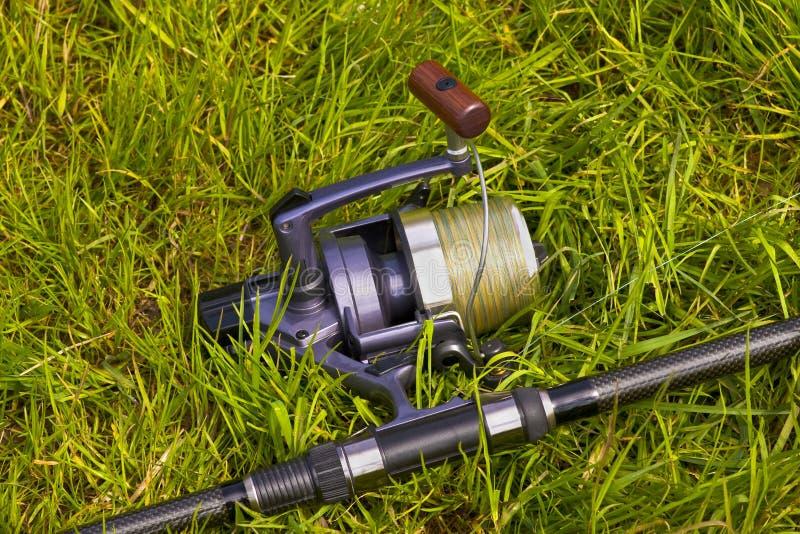 Bobine de pêche sur l'herbe images stock
