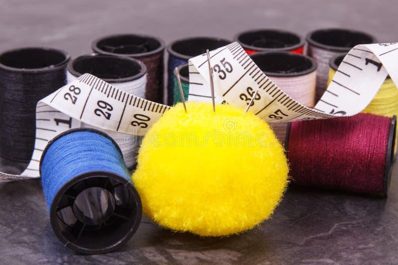 Bobine del filo, dell'ago e del centimetro Accessori per ricamo e cucire fotografie stock libere da diritti