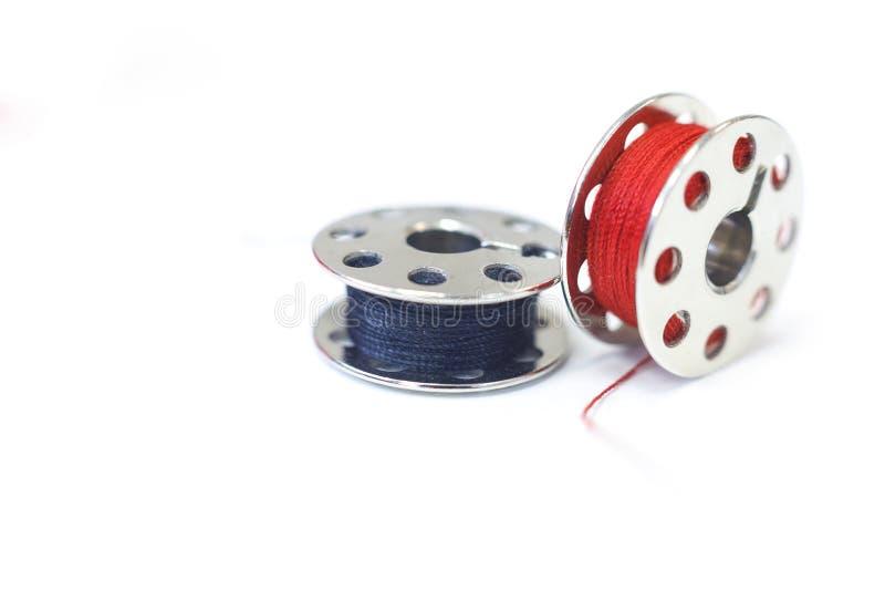Bobine di cucito con i fili rossi e blu scuro Macro fotografie stock