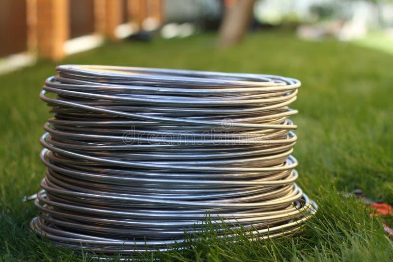 Bobine en aluminium de fil sur l'herbe Matériaux, industrie image stock