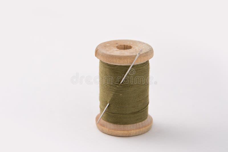 Bobine en bois de vintage avec des ficelles enroulées de couleur verte avec l'aiguille image stock
