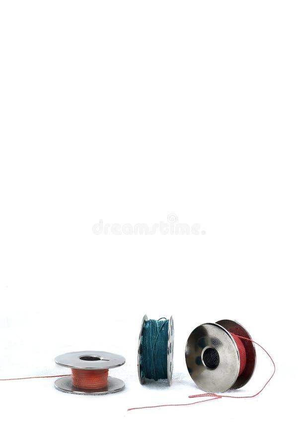 Bobine en métal avec les fils colorés sur le fond blanc photo libre de droits