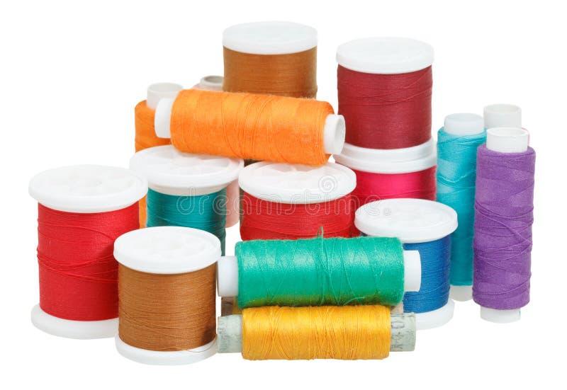 Bobine multicolori del filo isolate su bianco immagini stock