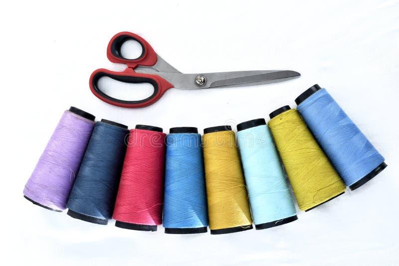 Bobine variopinte del filato cucirino su fondo bianco con le forbici fotografie stock libere da diritti