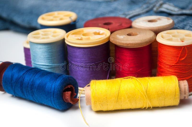 Bobine variopinte della bobina del filato cucirino su fondo bianco fotografia stock