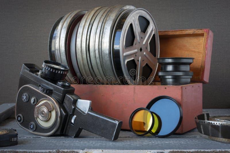 Bobines avec des films dans une boîte en bois, la lentille et un vieil appareil-photo de film image stock