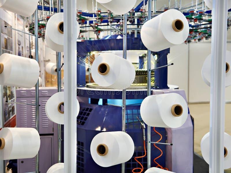 Bobines avec le fil blanc à l'usine de vêtement photo libre de droits