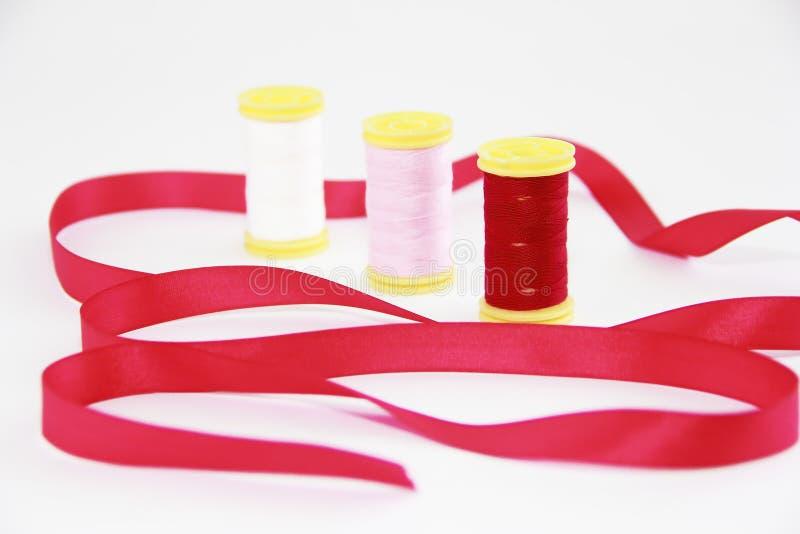 Bobines avec les fils blancs, rouges, roses multicolores et le ruban décoratif rouge images stock