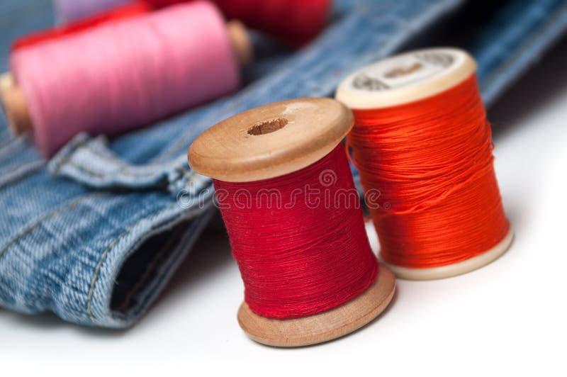 Bobines colorées de bobine de fil de couture sur la table blanche sur le fond de blues-jean photographie stock