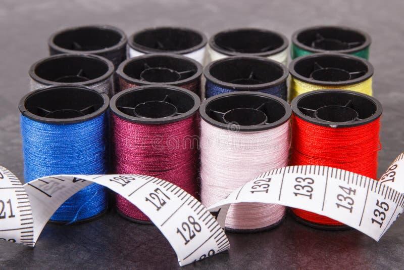 Bobines colorées de fil et de ruban métrique Accessoires pour la couture photographie stock