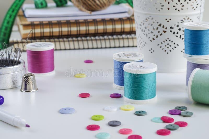 Bobines de fil et d'outils de couture de base comprenant les goupilles, l'aiguille, un dé et des boutons photos libres de droits