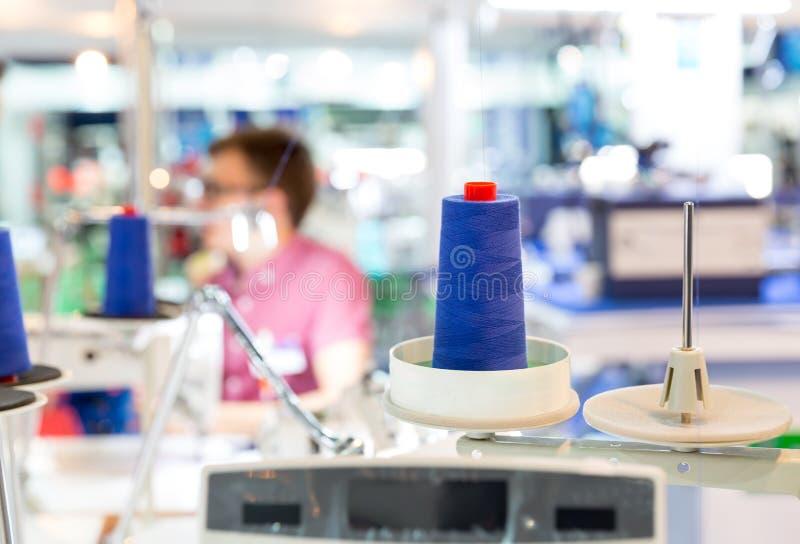 Bobines des fils bleus sur la machine à coudre, usine photo stock