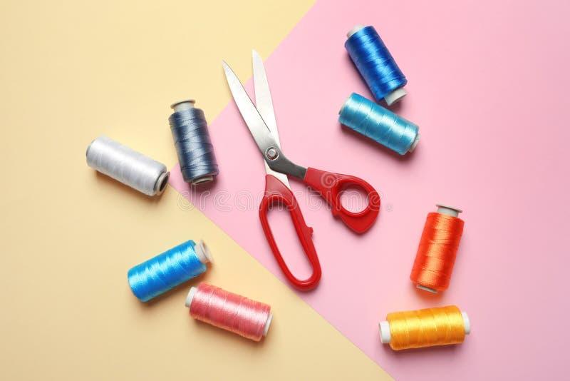 Bobiny nici i szwalni nożyce na koloru tle, zdjęcie royalty free
