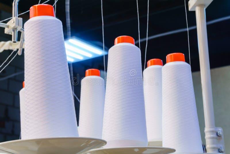 Bobiny z białymi niciami zabezpieczać w przemysłowej szwalnej maszynie obraz royalty free