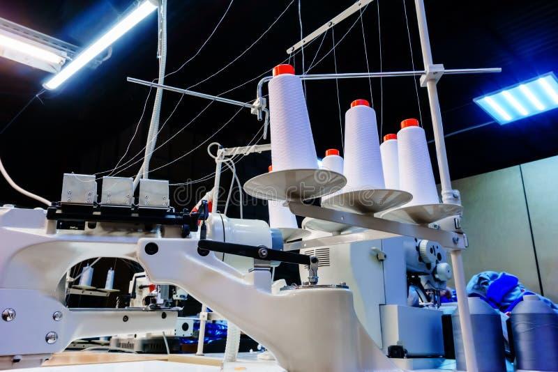 Bobiny z białymi niciami zabezpieczać w przemysłowej szwalnej maszynie zdjęcia royalty free