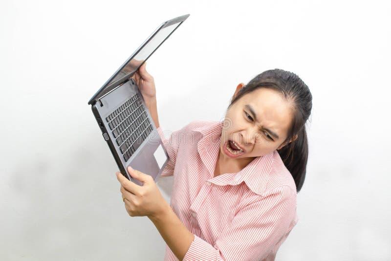 Boca aberta da mulher asiática irritada nova que grita aumentando o portátil até para jogá-lo afastado em um fundo branco imagens de stock