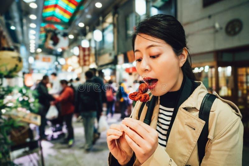 Boca abierta de la mujer que come poco pulpo dulce foto de archivo
