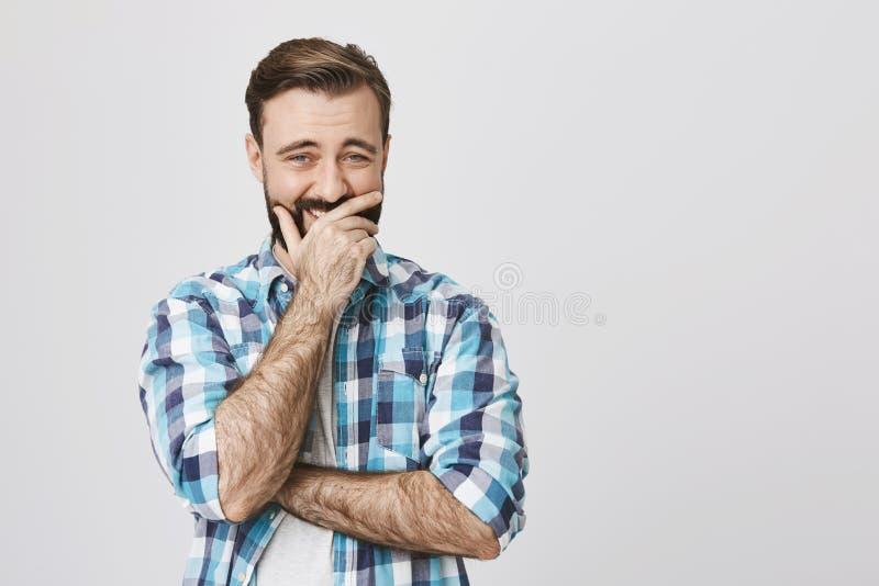 Boca barbuda hermosa de la cubierta del hombre con la mano que prueba no al laught ruidosamente sobre algo, oponiéndose a la pare imágenes de archivo libres de regalías