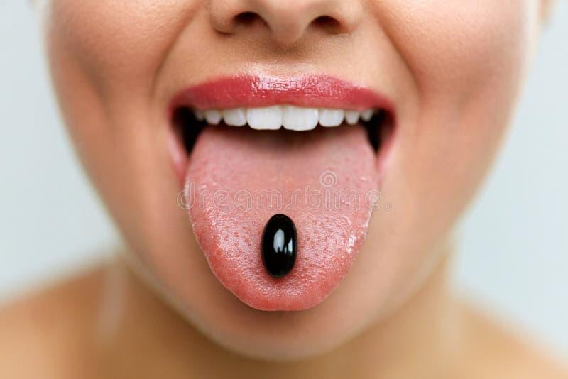 Boca bonita da mulher com o comprimido na língua Menina que toma a medicina imagens de stock royalty free