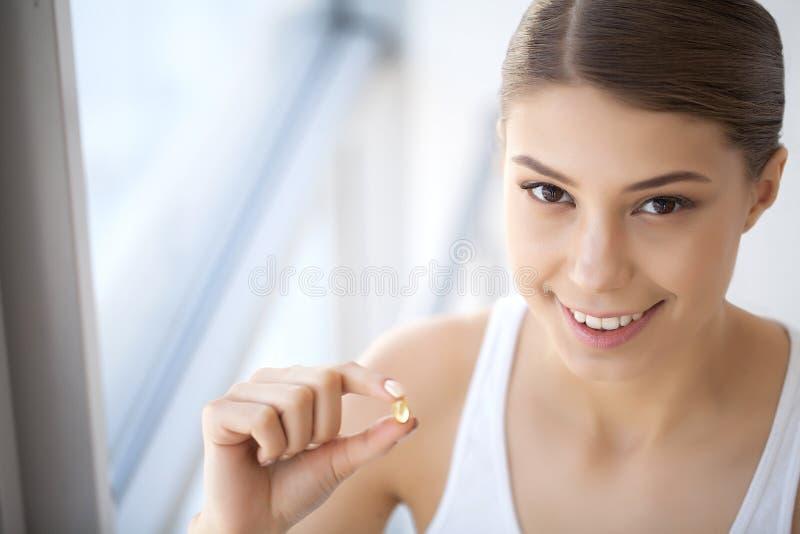 Boca bonita da mulher que guarda o comprimido para os dentes Menina que toma Vitami imagem de stock royalty free