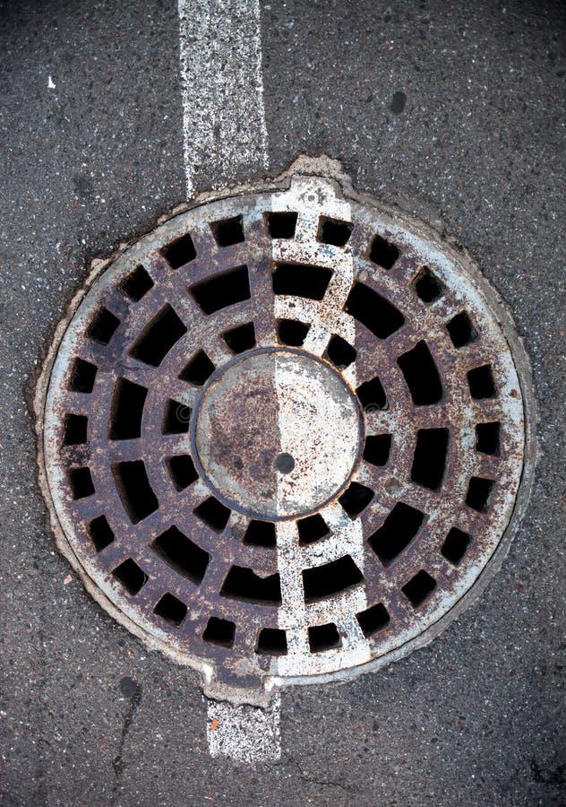 Boca con la cubierta del metal en asfalto con la línea blanca de la marca de camino foto de archivo