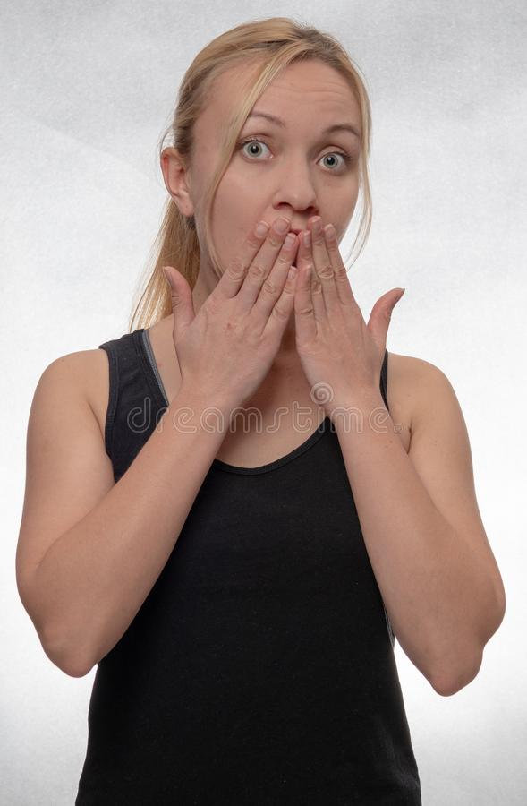 Boca da coberta da mulher nova com suas mãos foto de stock