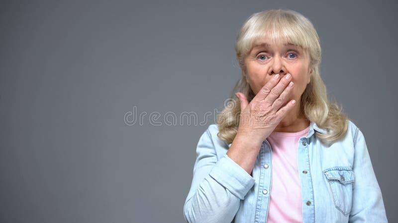 Boca de envejecimiento chocada de la cubierta de la mujer con la mano, asombrosa con noticias, emociones fotografía de archivo
