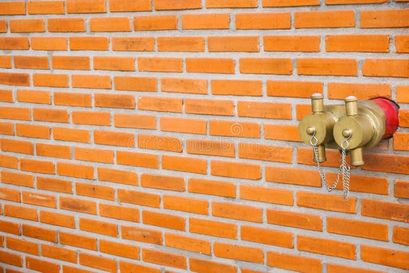 Boca de incêndio de fogo vermelho do ouro na parede de tijolo na construção moderna imagens de stock royalty free