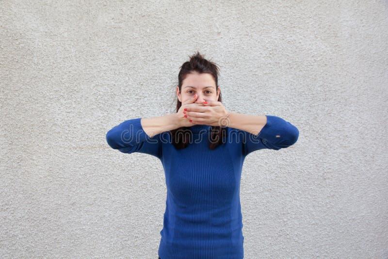 Boca de la cubierta de la mujer con las manos imágenes de archivo libres de regalías