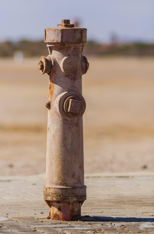 Boca de riego rojo marrón oxidada vieja que se coloca en el desierto imagenes de archivo