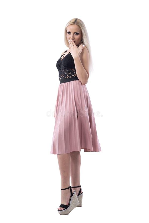 Boca elegante rubia joven sorprendente o chocada de la cubierta de la mujer con la mano que mira la cámara fotografía de archivo