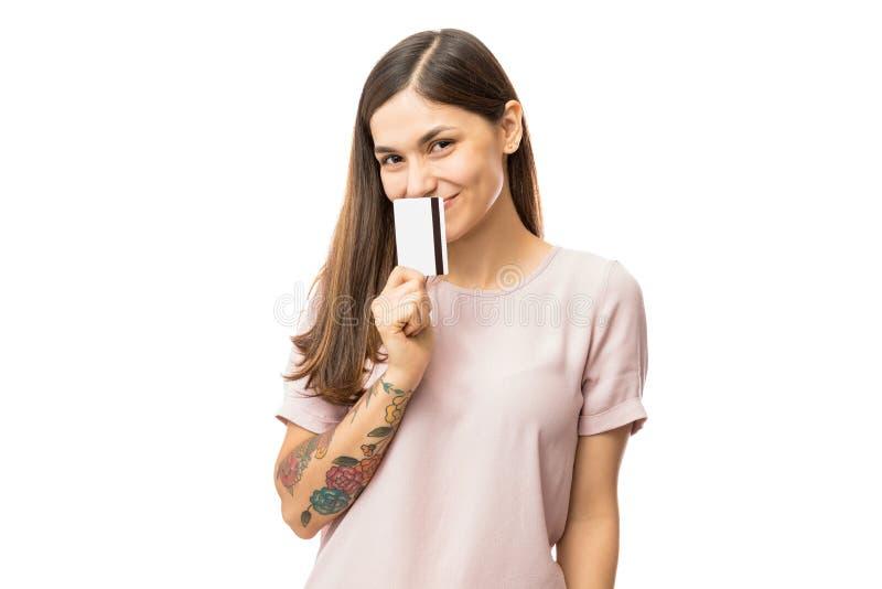 Boca feliz de la cubierta de la mujer joven con la tarjeta de crédito fotografía de archivo libre de regalías