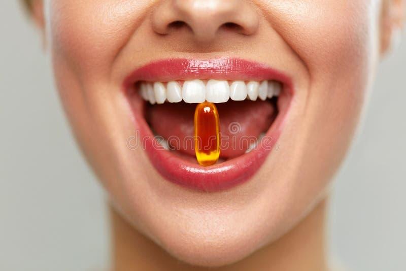 Boca hermosa de la mujer con la píldora en dientes Muchacha que toma las vitaminas fotos de archivo libres de regalías