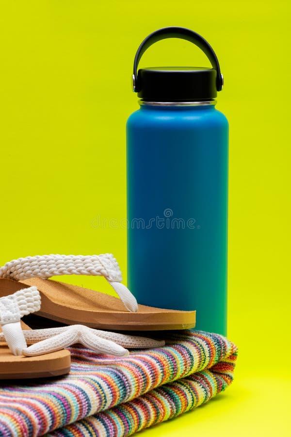 A boca larga azul isolou a garrafa de aço inoxidável, Flip Flops causal das mulheres, a toalha de praia colorida e a estrela do m fotos de stock