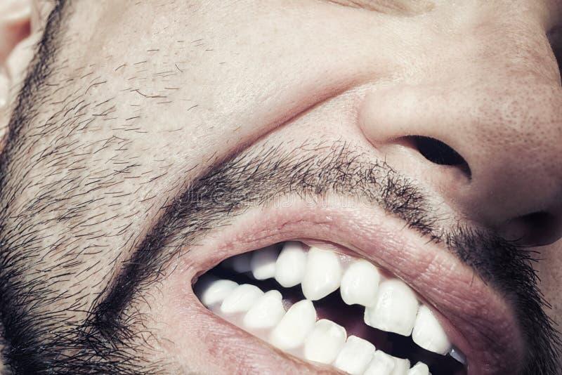 Boca masculina com dentes descobertos imagens de stock