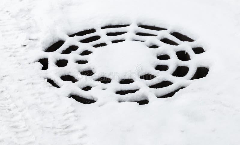 Boca redonda de la alcantarilla con nieve imagenes de archivo