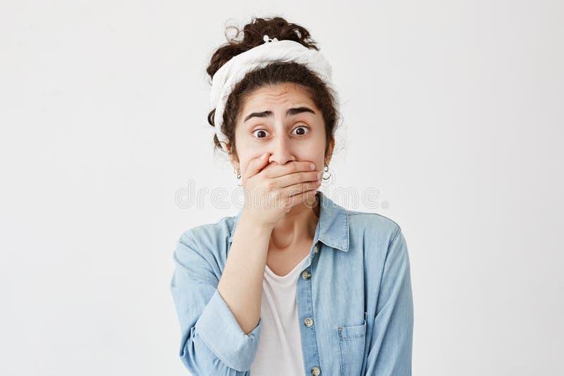 Boca vestindo moreno nova assustado chocada da coberta da camisa de fazer-pano e de sarja de Nimes com a mão que mantém um segred fotografia de stock